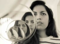 woman looking in set of mirrors with many reflections